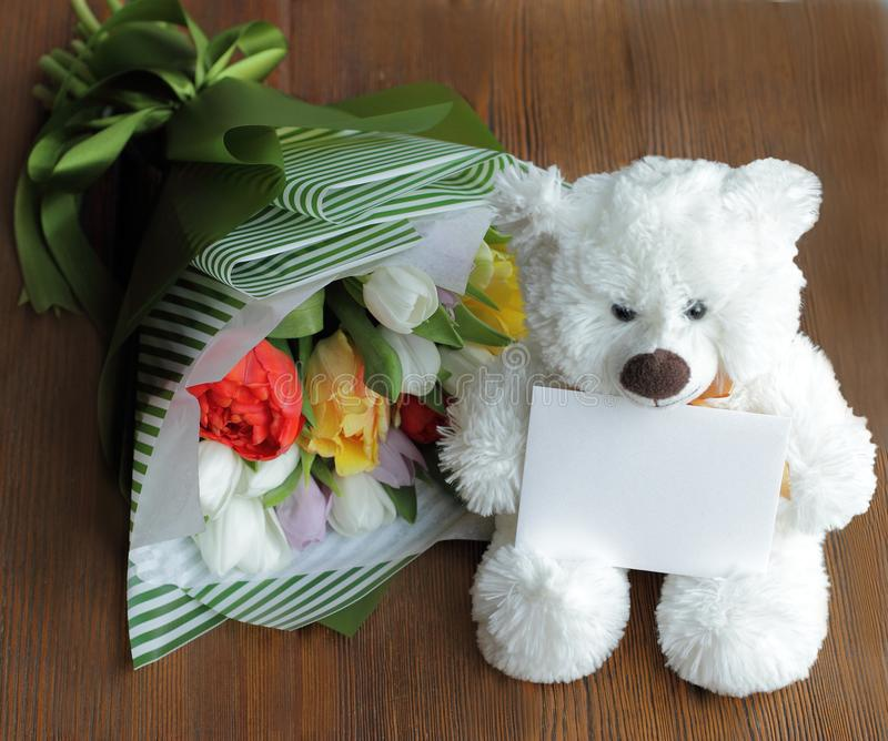 teddy bear with post card, your text, and red, yellow, lilac, white tulips royalty free stock photo
