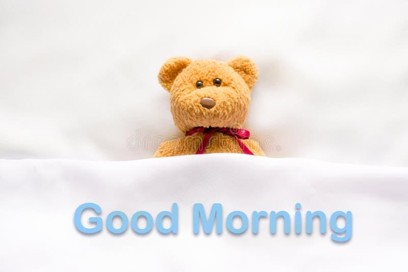 Teddy Bear que encontra-se na cama branca com mensagem & x22; Bom dia & x22; foto de stock royalty free