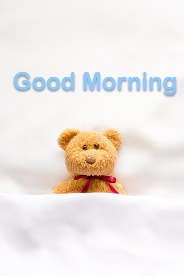 Teddy Bear que encontra-se na cama branca com mensagem & x22; Bom dia & x22; fotografia de stock