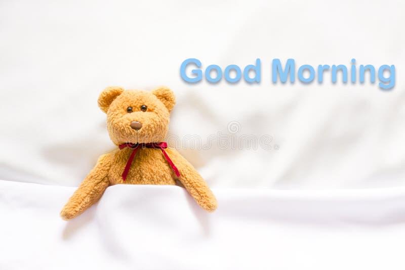 Teddy Bear que encontra-se na cama branca com mensagem & x22; Bom dia & x22; imagens de stock royalty free