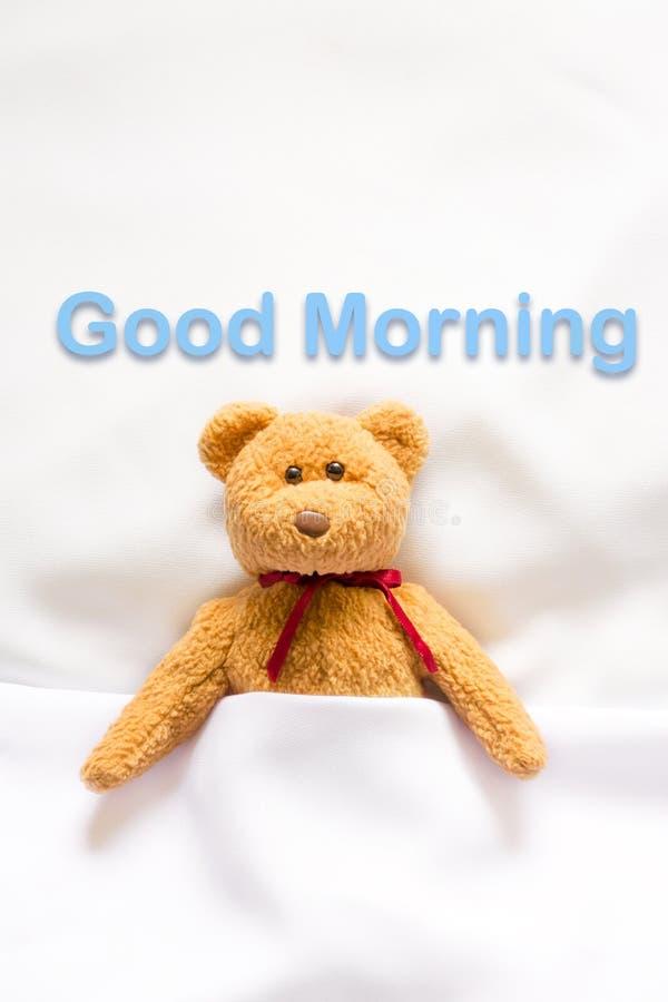 Teddy Bear que encontra-se na cama branca com mensagem & x22; Bom dia & x22; imagens de stock