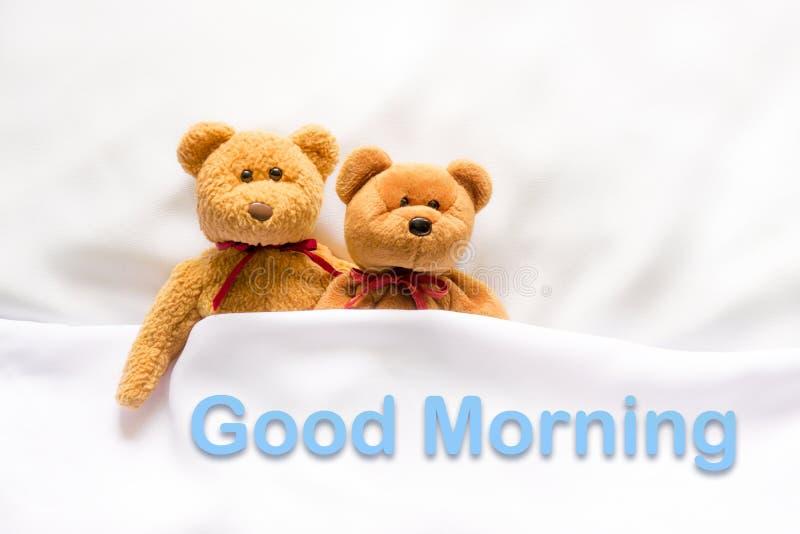 Teddy Bear que encontra-se na cama branca com mensagem & x22; Bom dia & x22; fotos de stock
