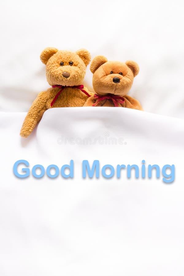 Teddy Bear que encontra-se na cama branca com mensagem & x22; Bom dia & x22; fotografia de stock royalty free