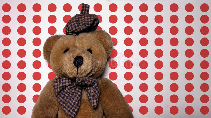Teddy bear with red polka dots background. Portrait of brown teddy bear with blue hat stock images
