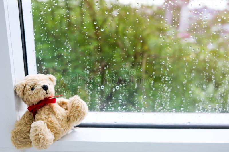Teddy Bear with red ribbon bow Sit sadly by the window And outside, it`s raining and cold. Teddy Bear with red ribbon sitting next to window With rain on the stock photos