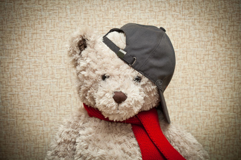 Teddy bear in a red scarf and a black baseball cap. Plush toy royalty free stock image
