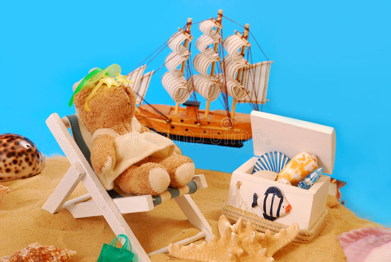 Teddy bear relaxing on the beach. Funny scene with little teddy bear relaxing on the beach lying on deckchair stock images