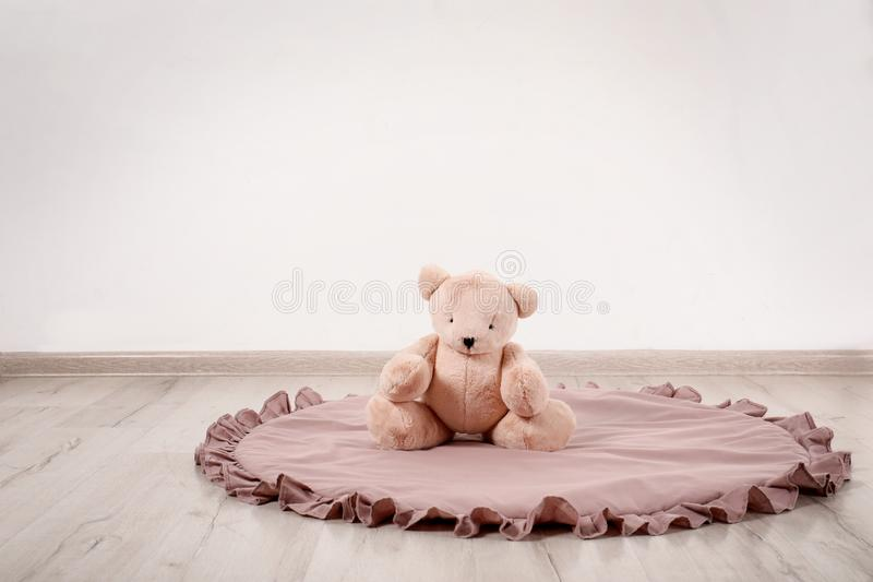 Teddy bear and rug on floor in child room. stock photo