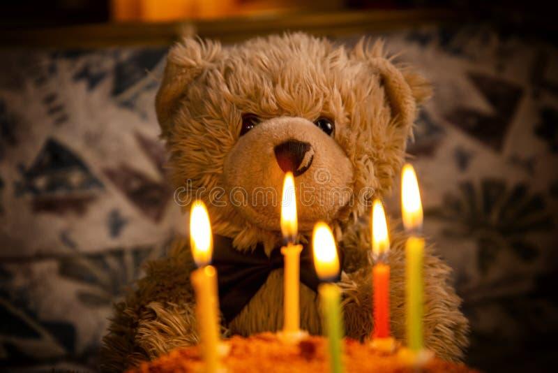 Teddy bear`s birthday. Teddy bear with festive cake with candles stock image