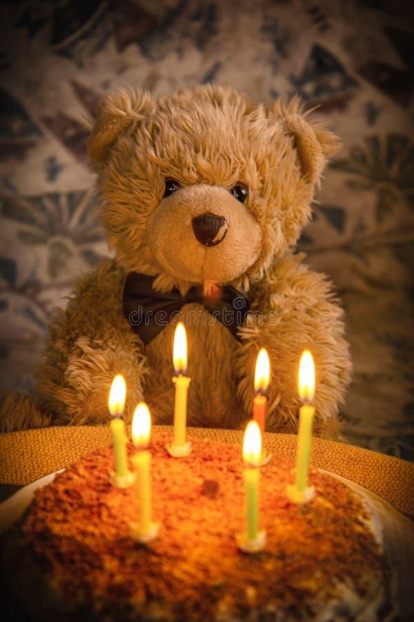 Teddy bear`s birthday. Teddy bear with festive cake with candles royalty free stock photos