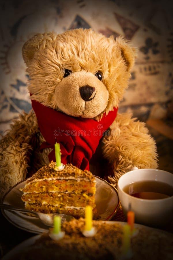 Teddy bear`s birthday. Teddy bear with festive cake with candles stock images