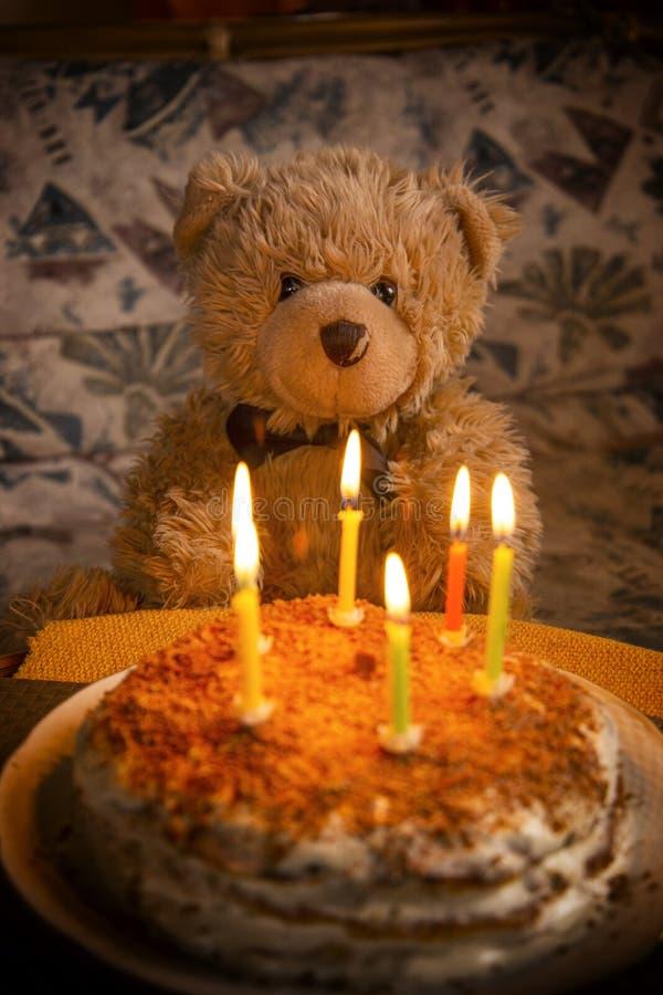Teddy bear`s birthday. Teddy bear with festive cake with candles stock photography