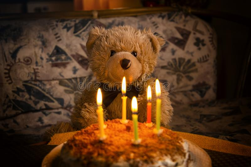 Teddy bear`s birthday. Teddy bear with festive cake with candles royalty free stock images