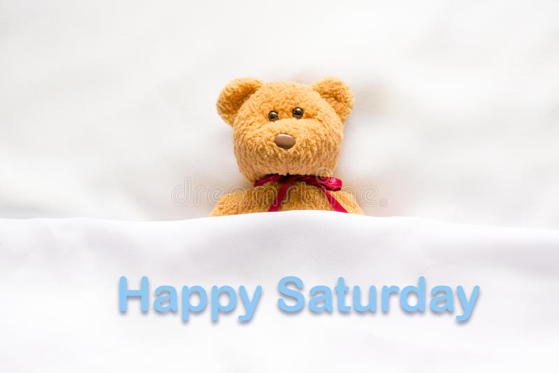 Teddy Bear se situant dans le lit blanc avec le message et le x22 ; Saturday& heureux x22 ; photographie stock