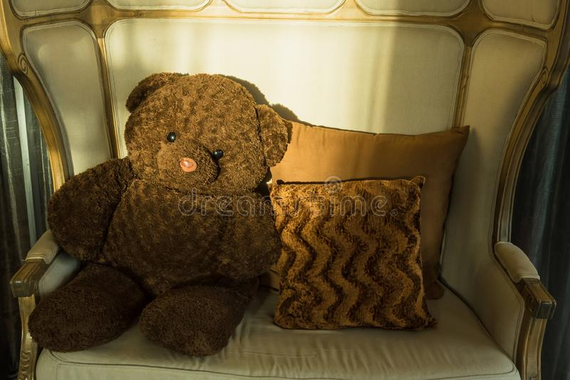 Teddy bear sit alone, Teddy Bear sitting on chair with sun light morning.Thailand royalty free stock images