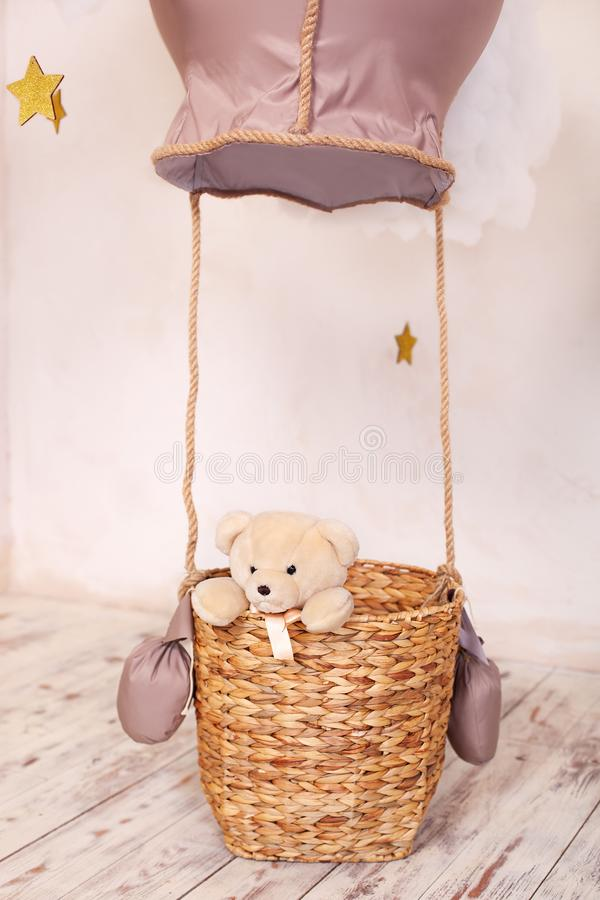 Teddy bear sitting in the balloon basket, aerostat. Children`s location for a photo shoot: a balloon and clouds. The child plays t. He traveler. Rest of the stock photo