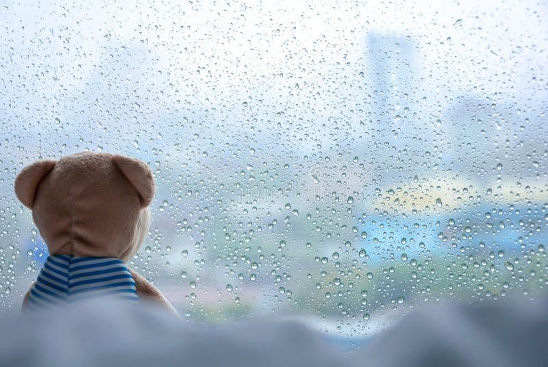 Teddy Bear solo que se sienta en cama y que mira hacia fuera la ventana en día lluvioso fotografía de archivo libre de regalías
