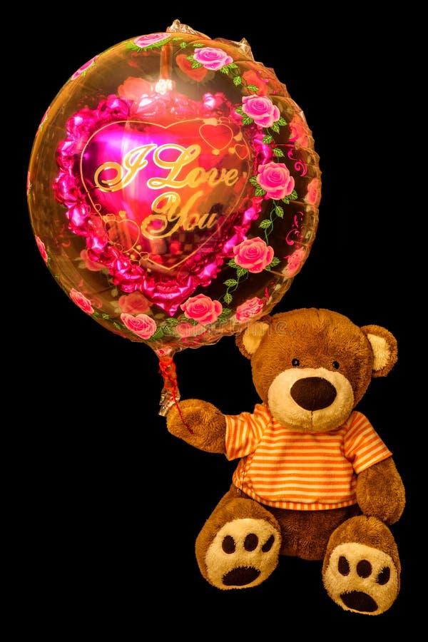 Teddy Bear som rymmer den röda hjärta-formade ballongen Valentinbjörn med royaltyfri fotografi