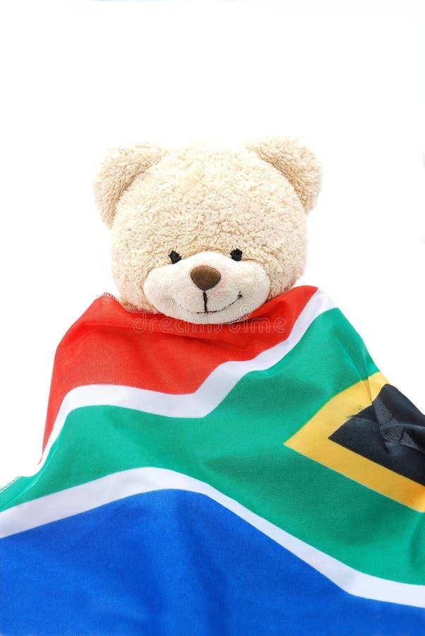 Teddy bear with South African flag. A cute beige teddy bear wearing the South African flag stock photography