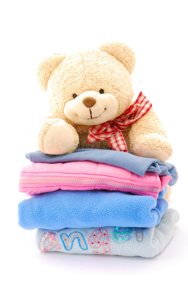 Teddy bear stack of kids clothes. A cute little teddy bear looking over a stack of colorful kids clothes. Image isolated on white studio background stock photo