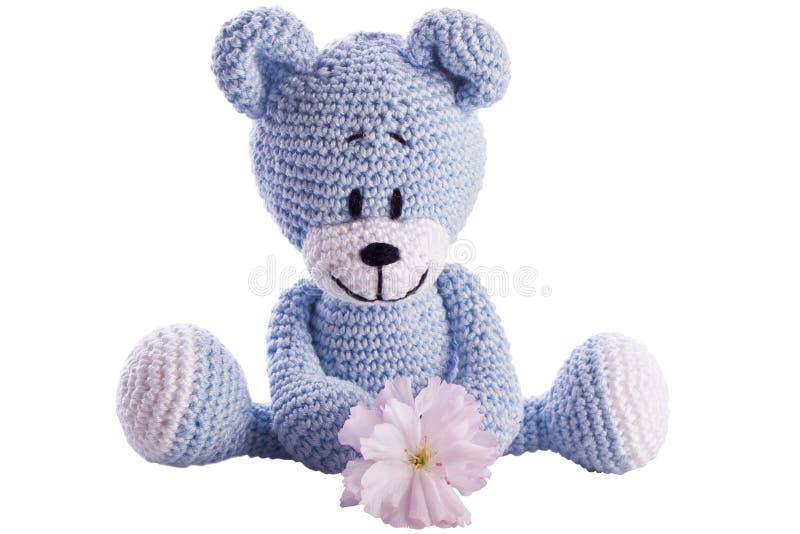 Teddy bear stuffed animal with pink blossom stock image