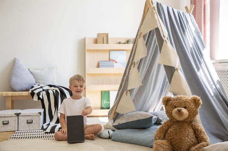 Teddy bear and tent in a playroom interior where a young boy is playing. Teddy bear and tent in a playroom interior where young boy is playing stock photo
