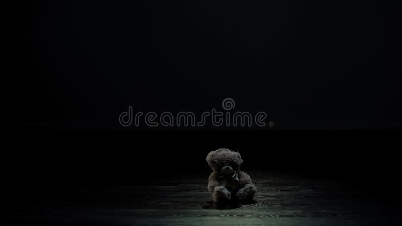 Teddy bear toy in dark room, loneliness and lost childhood concept, sadness stock images