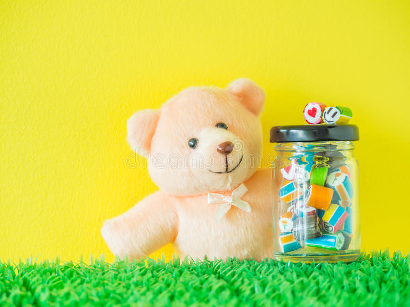 Teddy Bear toy looks at a red heart and green smiley face candy. Put on the top of glass jar with colorful candies royalty free stock photography