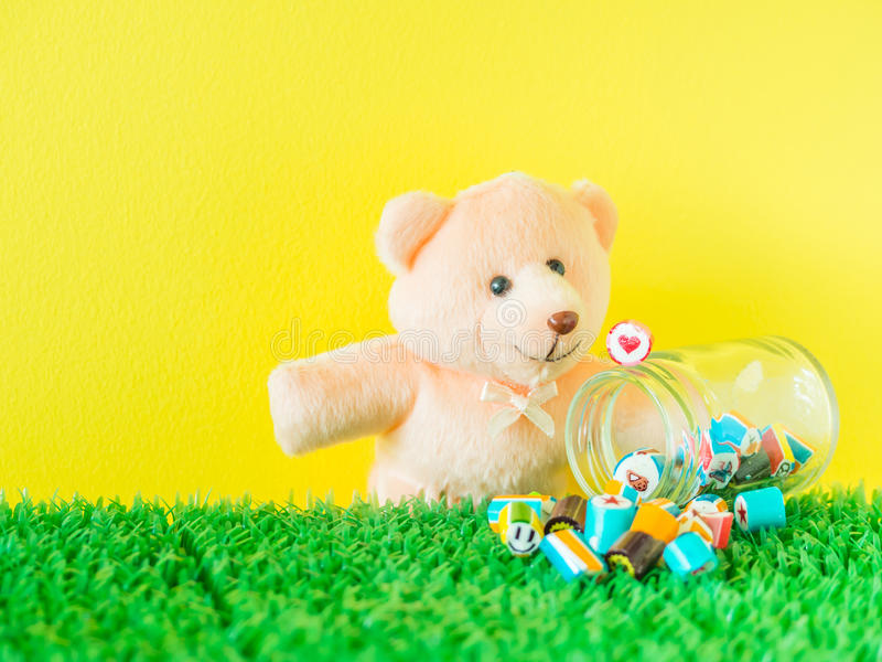 Teddy Bear toy looks at a red heart shape candy on glass jar.  stock photography