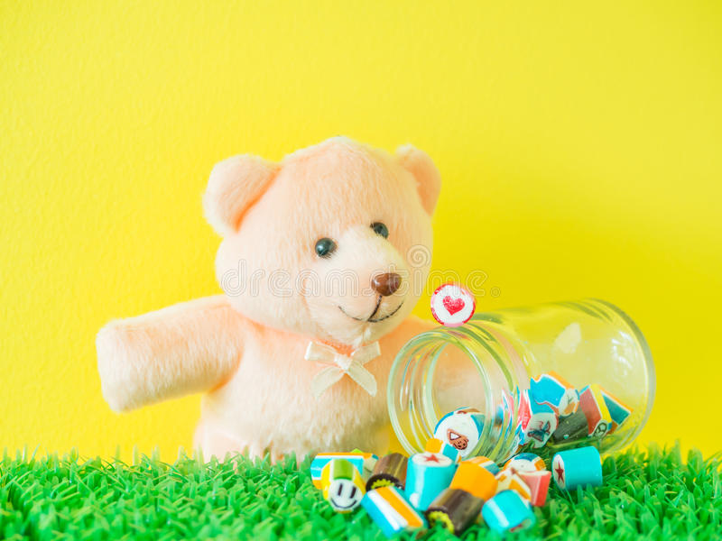 Teddy Bear toy looks at a red heart shape candy on glass jar. With colorful candies on artificial grass and yellow cement background royalty free stock image