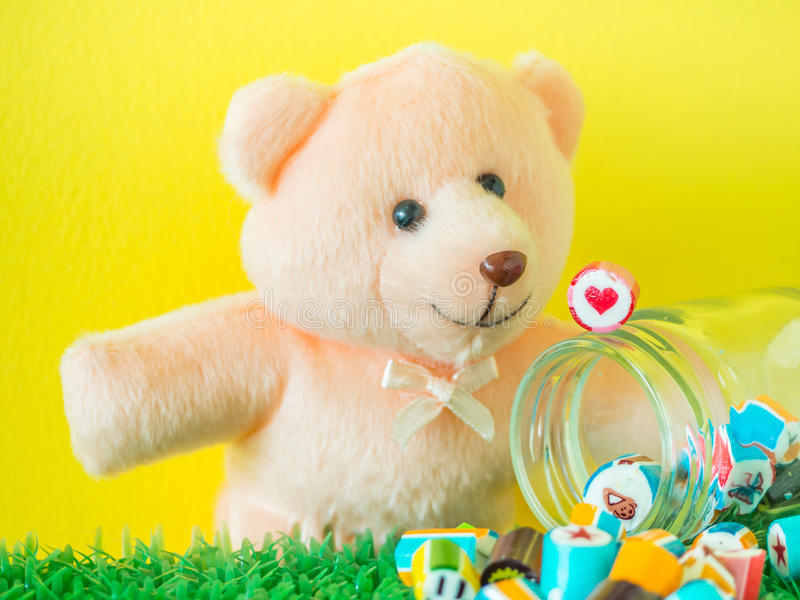 Teddy Bear toy looks at a red heart shape candy on glass jar. With colorful candies on artificial grass and yellow cement background royalty free stock images