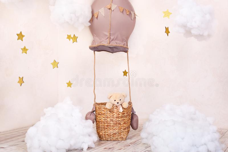 Teddy bear traveler and pilot. Childhood dreams. Stylish vintage children`s room with aerostat, balloons and textile clouds. Child. Ren`s location for a photo stock photography