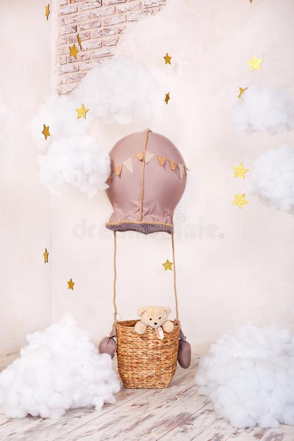 Teddy bear traveler and pilot. Childhood dreams. Stylish vintage children`s room with aerostat, balloons, textile clouds. Children. `s location for a photo shoot royalty free stock image