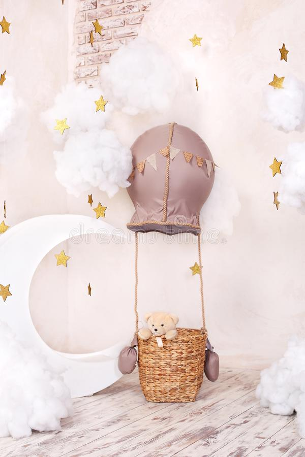Teddy bear traveler and pilot. Childhood dreams. Stylish vintage children`s room with aerostat, balloons, textile clouds and the m. Oon. Children`s location for stock photos
