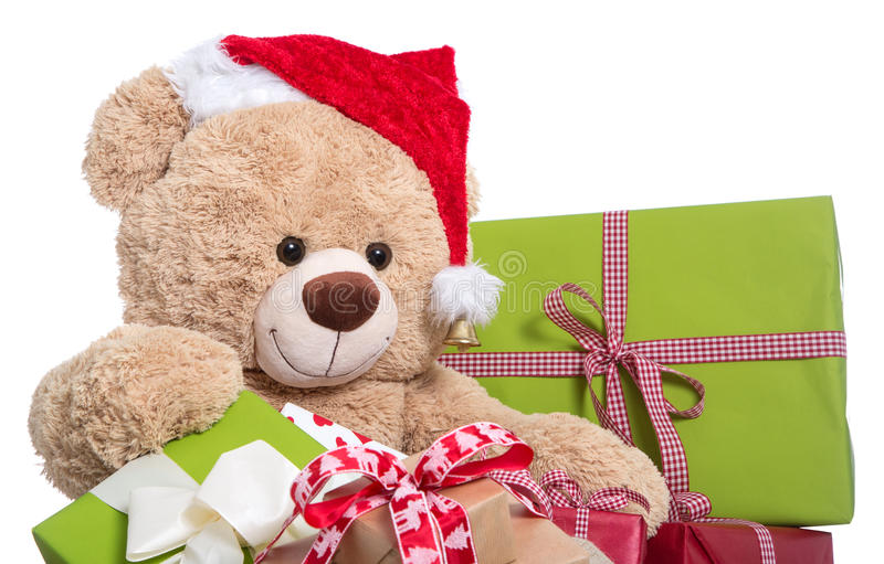 Teddy bear wearing Christmas hat with gifts on white background. Isolated teddy as a santa clause with presents in red and green royalty free stock images