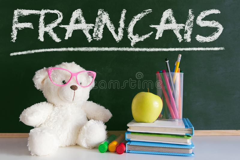 Teddy bear wearing glasses in a French language classroom next to an apple and a pile of books and a dictionary royalty free stock photo
