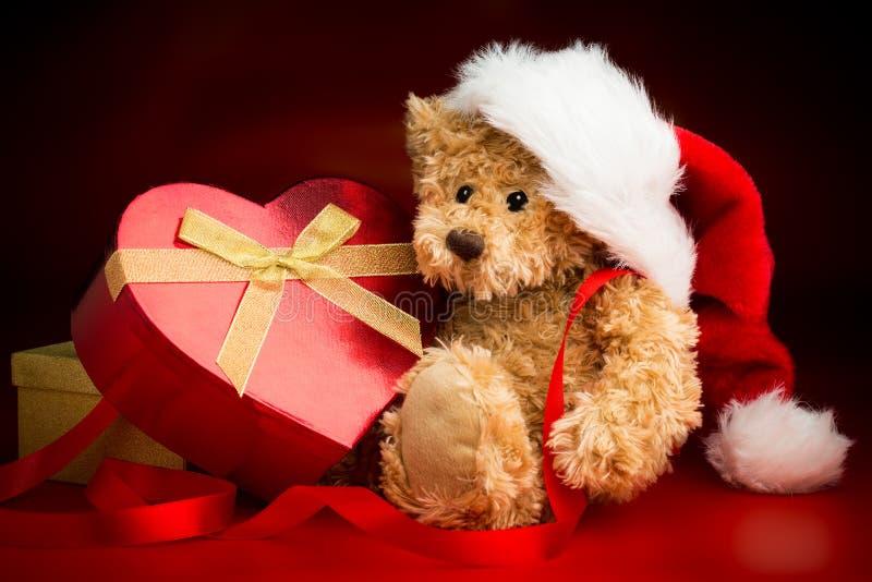 Teddy Bear Wearing um chapéu do Natal e aperto de uma caixa fotografia de stock royalty free