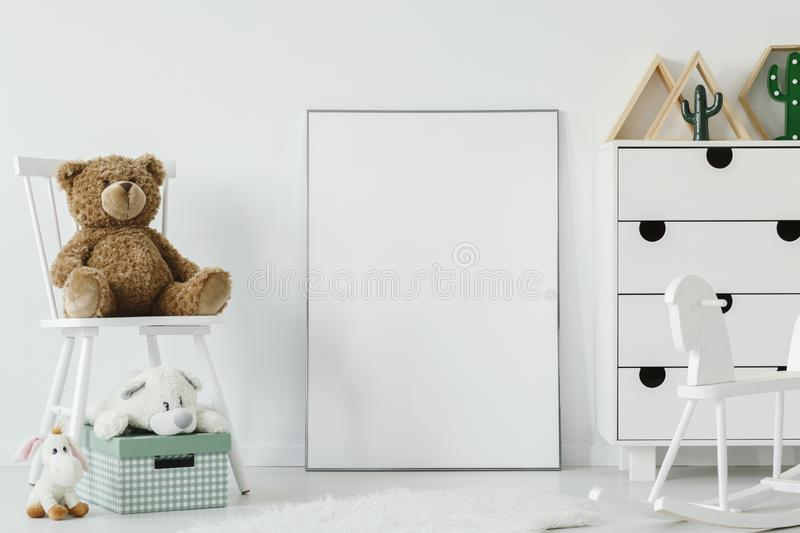 Teddy bear on white chair next to white poster with mockup in ch. Ild`s room interior. Real photo. Place for your graphic royalty free stock photography