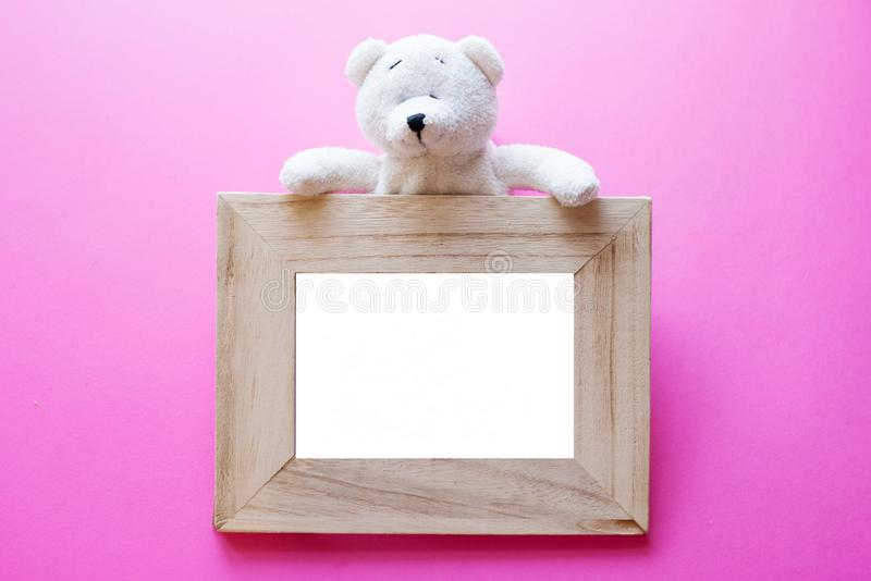 Teddy bear and wood photo frame on pink background. frame for kids. birthday concept stock images