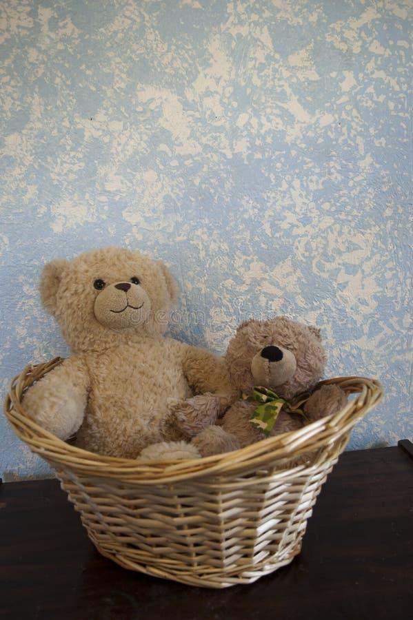 Teddy Bears classico contro una parete blu in un canestro fotografia stock libera da diritti