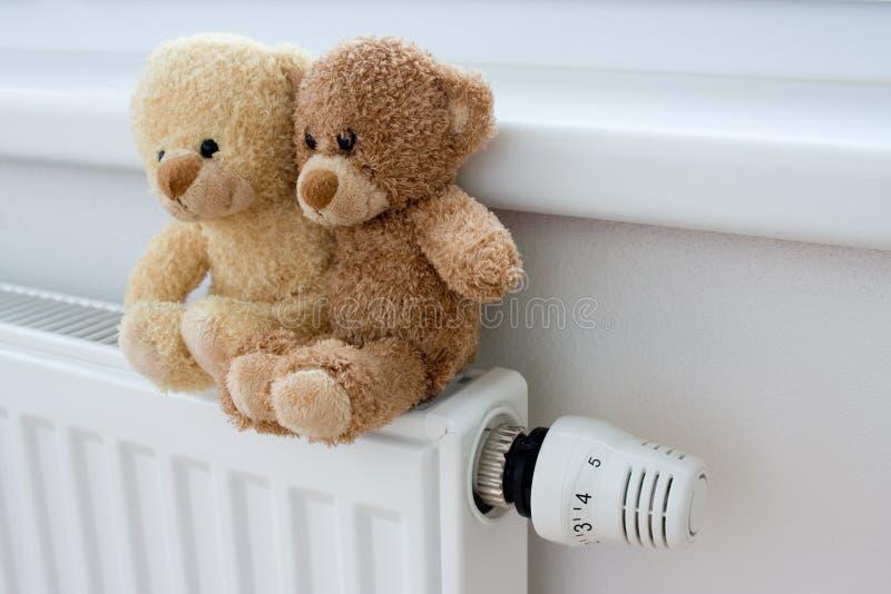 Teddy bears on the heater royalty free stock photos