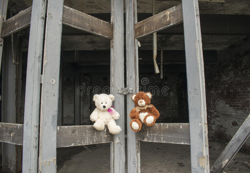 Teddy Bears Sitting On Abandoned Fie Station Bay Doors royalty-vrije stock foto