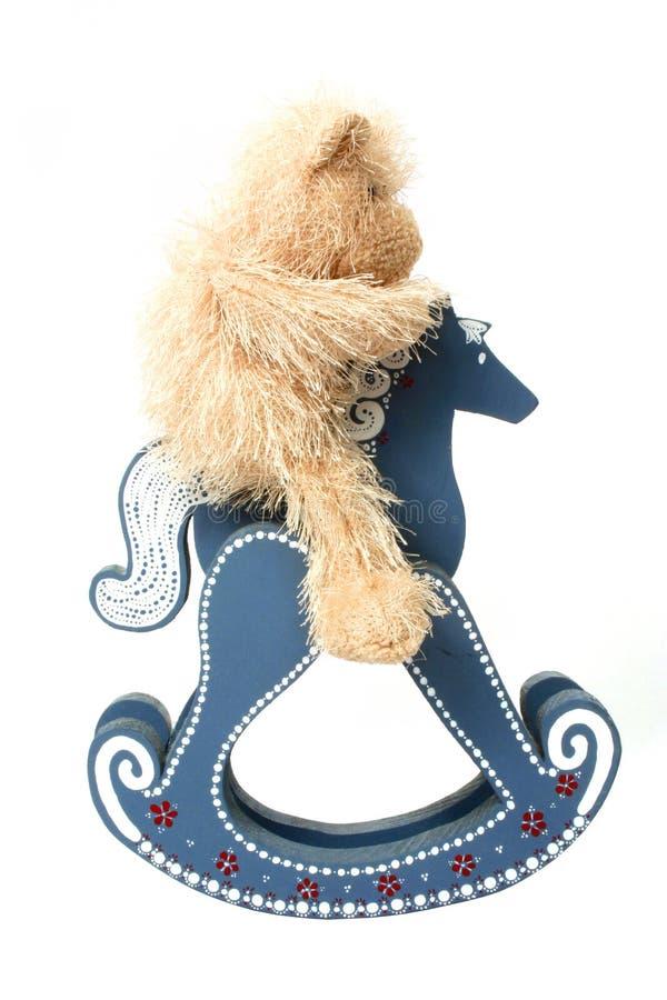 Teddy berijdt een Hobbelpaard stock foto's