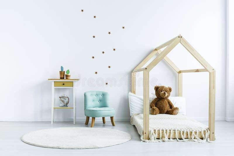 Teddybär betreffen hölzernes Bett nahe bei blauem Stuhl in weißem Kind-` s bedro stockfoto