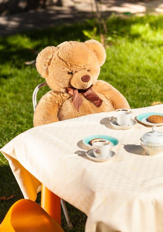 Teddybär, der hinter Tabelle und trinkendem Tee sitzt stockfotografie