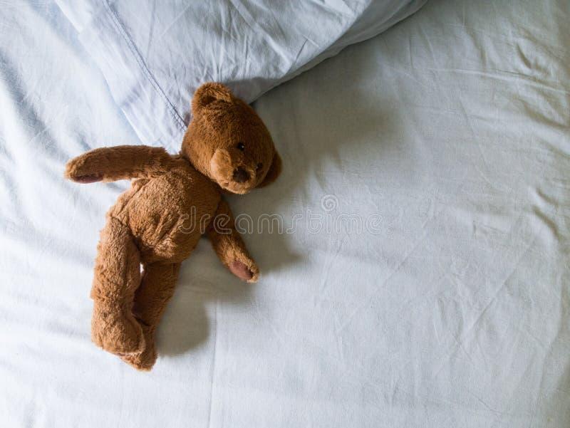 Teddybär gelassen auf Bett stockfoto