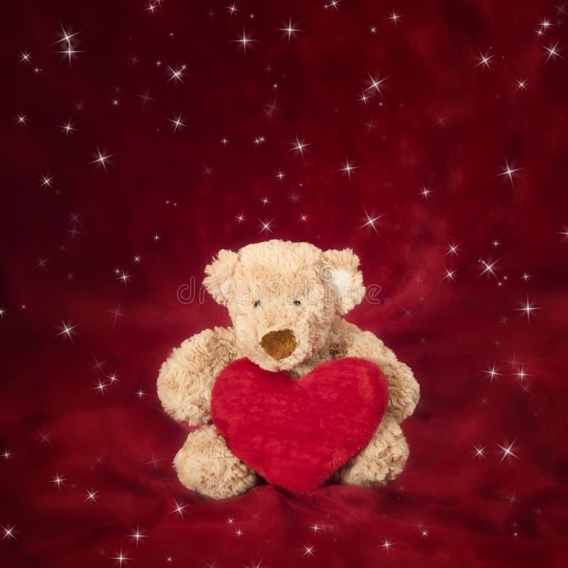 Teddybär mit geformtem Kissen des Inneren auf Rot lizenzfreie stockfotografie