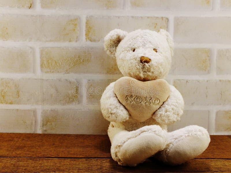 Teddybär mit Herzvalentinsgruß ` s Tag mit Raumhintergrund lizenzfreies stockbild