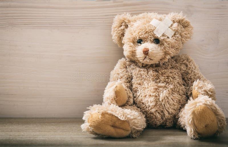 Teddybär mit Verband auf einem Bretterboden stockbilder