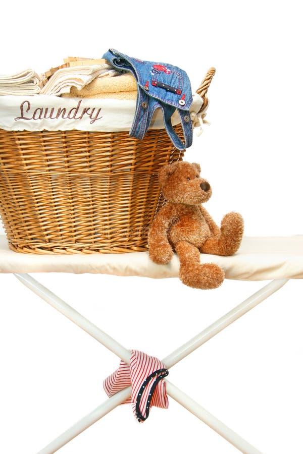 Teddybär mit Wäschereikorb auf bügelndem Vorstand lizenzfreie stockfotos